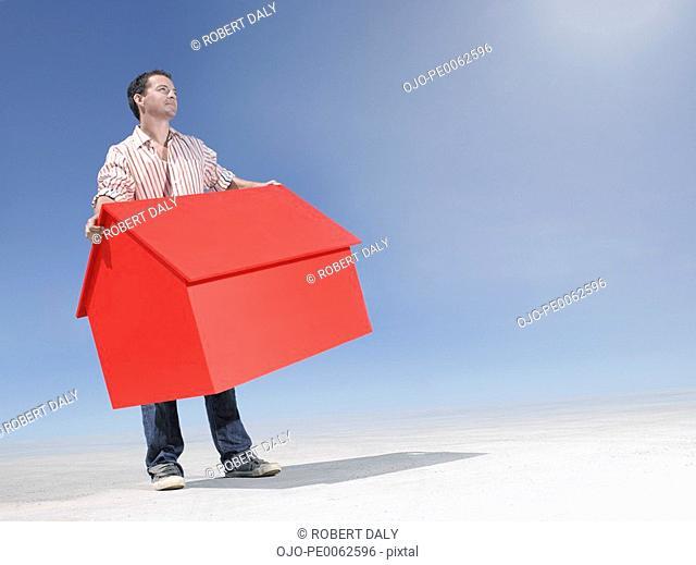 Man holding small model house in desert