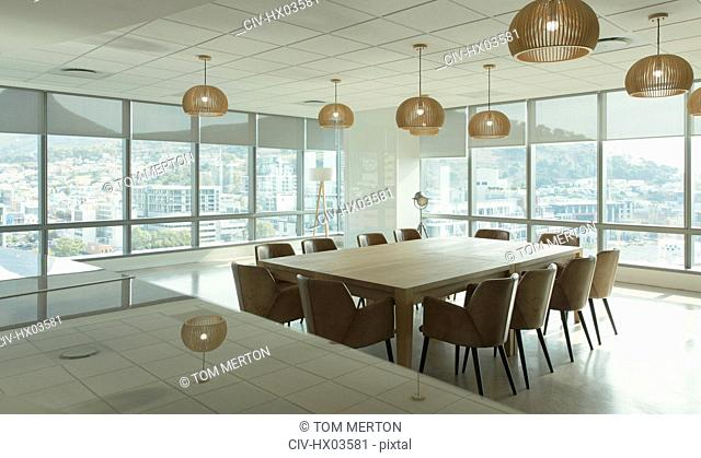 Conference table and pendant lights in modern office conference room