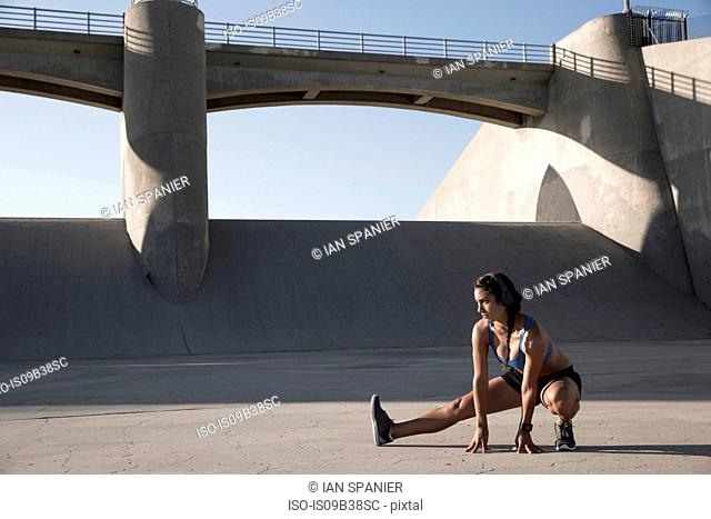 Female athlete with headphones, stretching, Van Nuys, California, USA