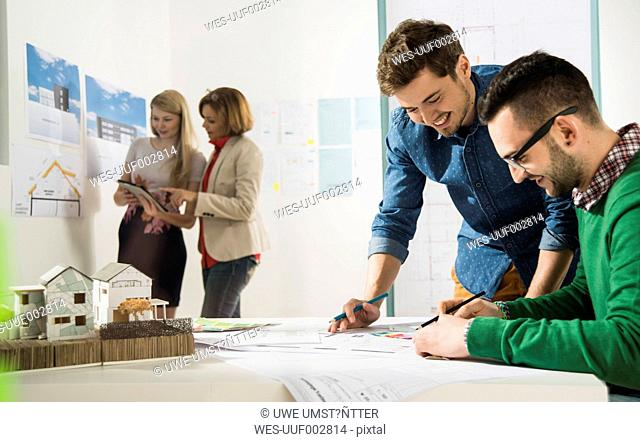 Young architects in office looking at construction plan