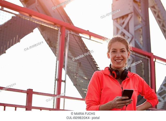 Young woman outdoors, wearing headphones around neck, using smartphone