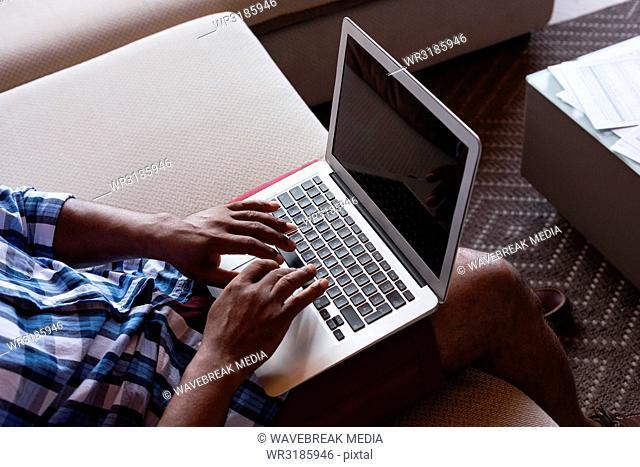 Senior man sitting on sofa while using laptop