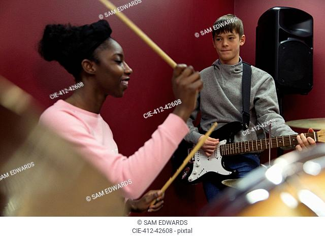 Teenage musicians recording music, playing guitar and drums in sound booth