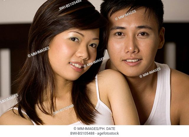 A happy looking asian couple pose on a bed