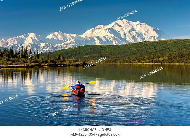 A man kayaking on Wonder Lake in Denali National Park with Denali in the background, Interior Alaska, summer