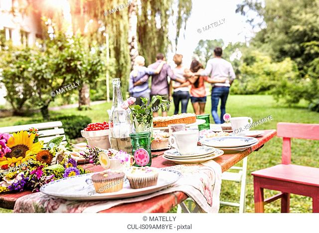Group of friends walking away with arms around each other, garden party table with food in foreground