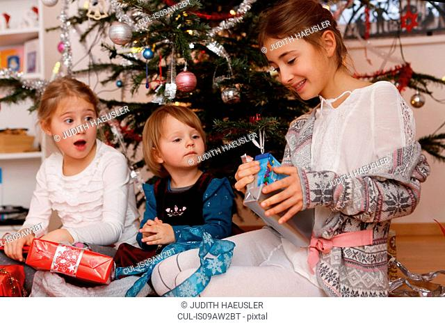 Girls in front of christmas tree opening gifts