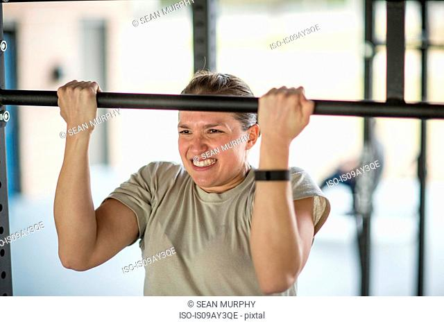 Determined female soldier doing pull ups at military air force base