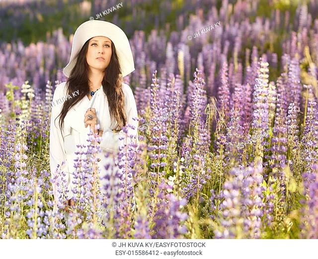 Fashionable young woman wearing a white hat and jacket, summery meadow