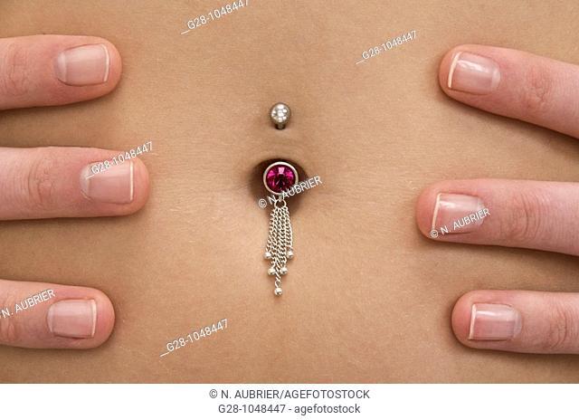 woman's tummy pierced with jewel close up