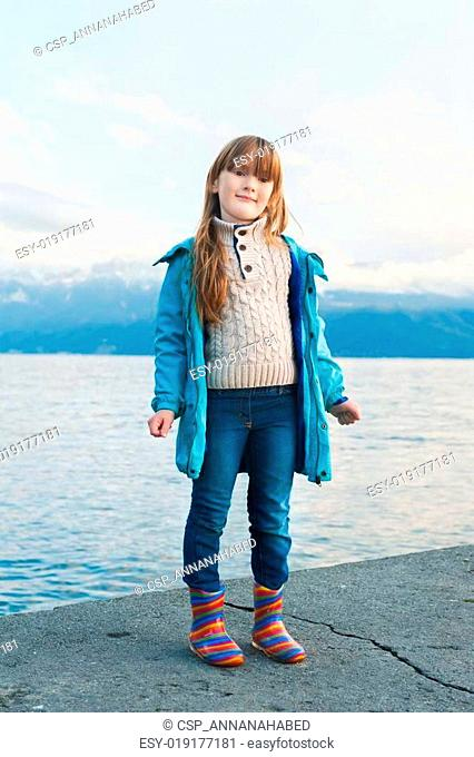 Outdoor portrait of a cute little girl resting by the lkae, wearing blue coat and colorful rain boots