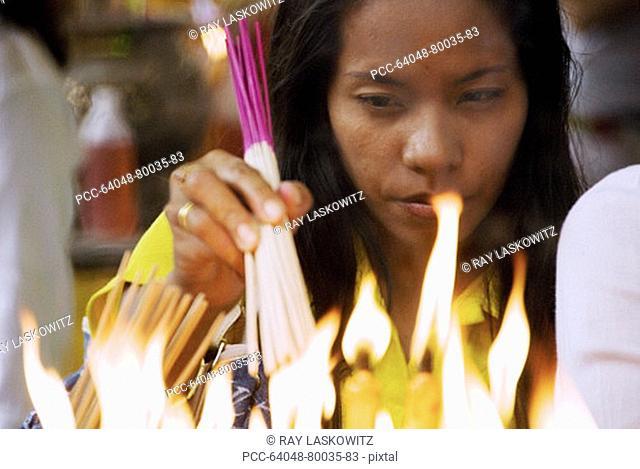 Thailand, Bangkok, Yarowat Chinatown, Wat Mangkon Kamalawat, Vegetarian Festival, Woman lighting candles as an offering