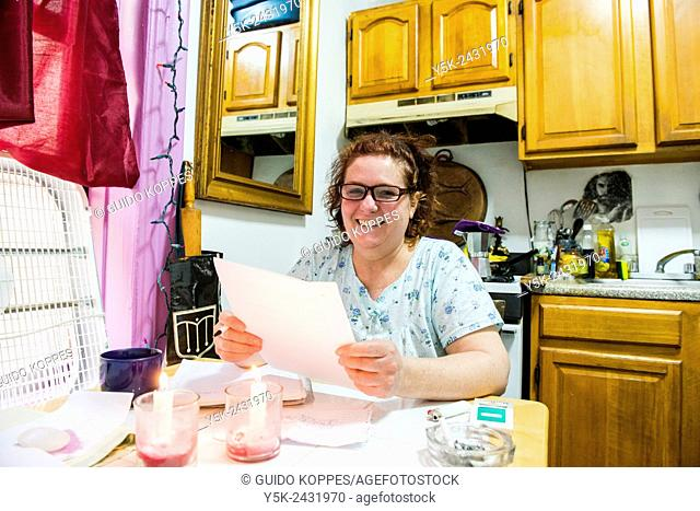 New York, USA. Female Airbnb hostess, working on her kitchen table in her Brooklyn based Airbnb guest house
