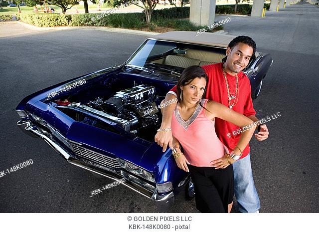 Portrait of a young hip-hop couple standing beside a pimped-up vintage car