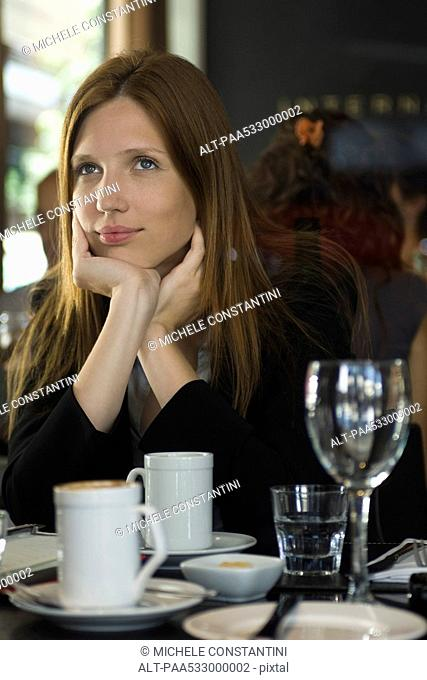 Woman sitting in cafe, daydreaming