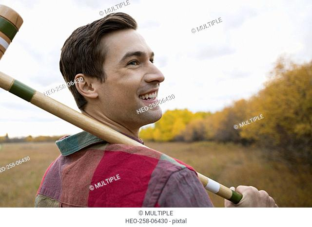 Smiling young man with croquet mallet