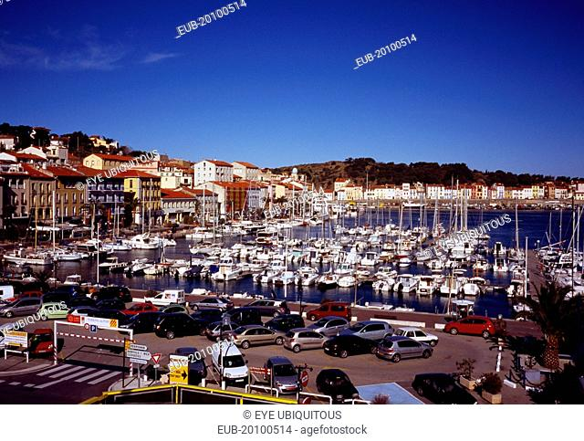 Port-Vendres. Inner harbour with moored boats quay and quayside buildings with car park in foreground. Hillside part visible beyond