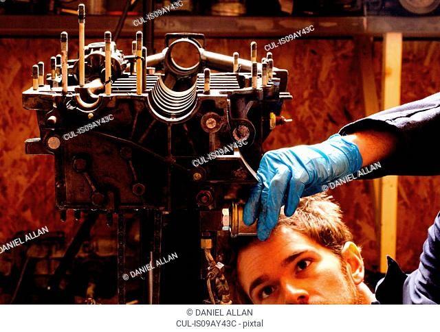 Male mechanic repairing car engine, stripped from car