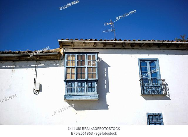 Facade with balcony, bowindow and typical window of a village house. Province of Leon, Camino de Santiago, Spain