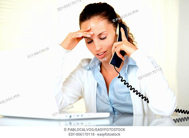 Stressed young woman with headache speaking on phone in front of laptop at workplace