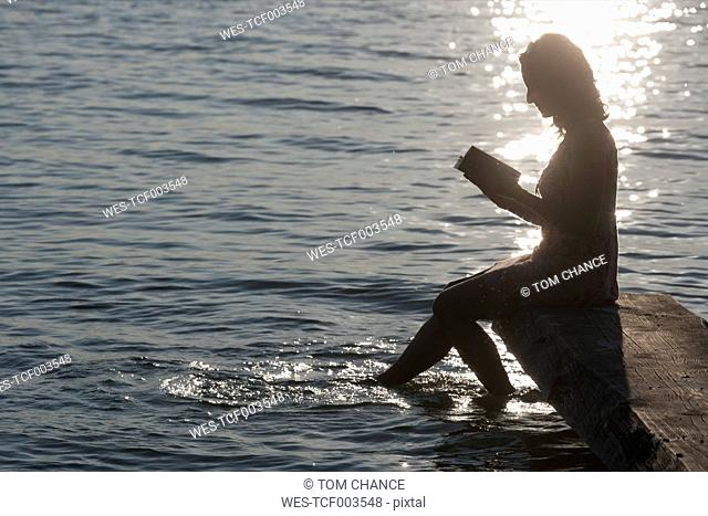 Germany, Bavaria, Mature woman reading book at Lake Stamberg