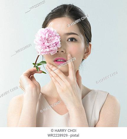 Woman with pink lip make-up holding a pink flower covering her eye with the other hand on her face