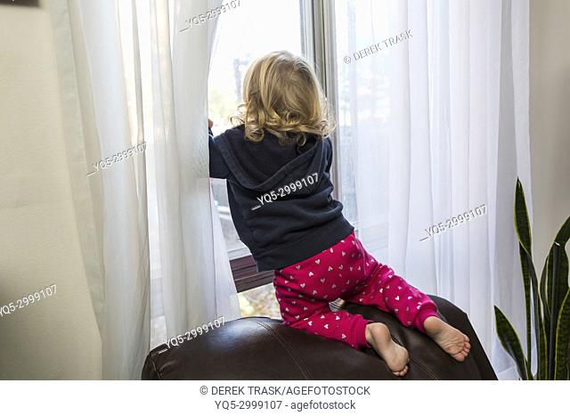 2 year old child looking out window at risk of falling out after climbing on chair