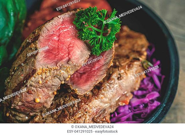 Steak rare with the blood, pepper, Dijon mustard, braised red cabbage and parsley, grilled in a pan at home. Selective focus. The horizontal frame