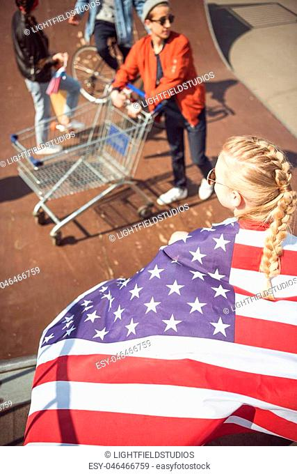Blonde young girl with american flag looking at friends having fun at skateboard park