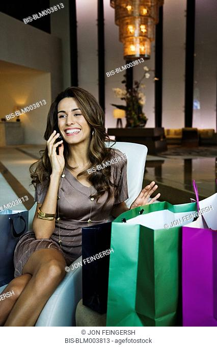 Hispanic woman talking on cell phone and surrounded by shopping bags