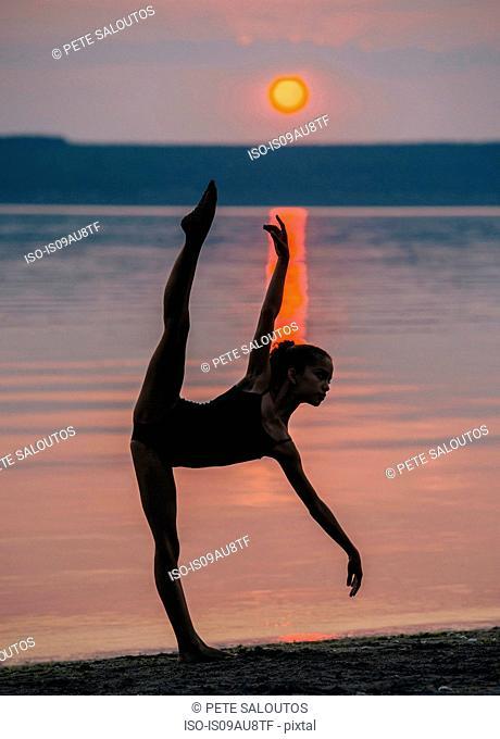 Girl by ocean at sunset on one leg, bending forward arm and leg raised