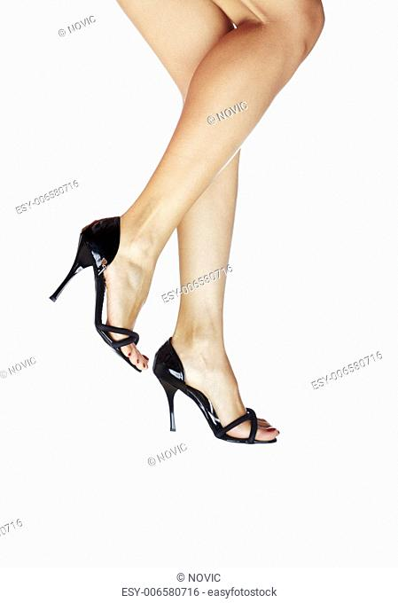 Woman legs walking in black shoes on a white background