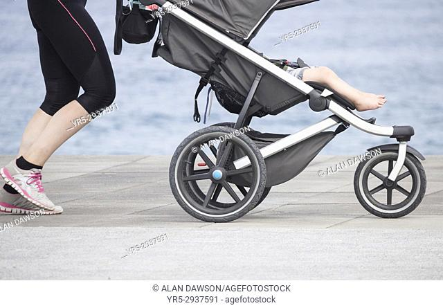 Young woman jogging with baby/child in stroller/pushchair. Gran Canaria, Canary Islands, Spain