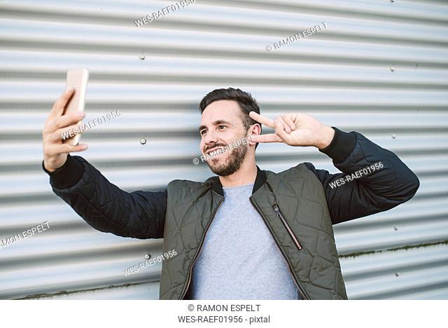Portrait of smiling man taking selfie with smartphone showing victory sign
