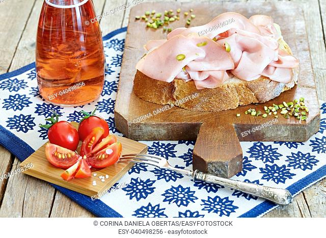 Fresh cut mortadella with pistachio nuts on bread slice, together with cherry tomatoes and rose sparkling wine
