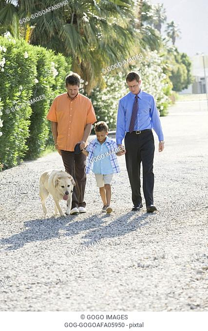 Gay couple walking with their son
