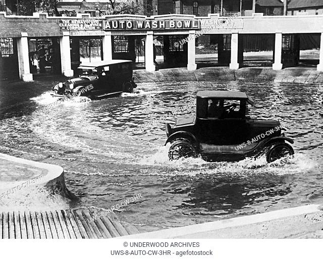 Chicago, Illinois: September 20, 1924.A new method of washing autos in Chicago. Two cars at a time run through the Auto Wash Bowl to clean the mud and dirt from...