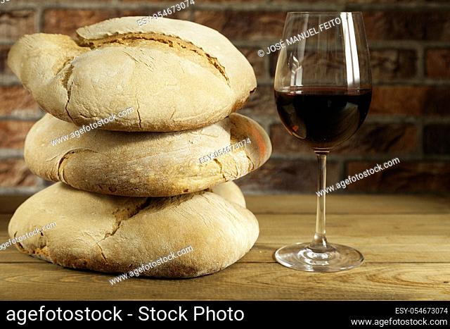 Glass of red wine and three loaves of rustic bread one on another on wooden table and red brick background