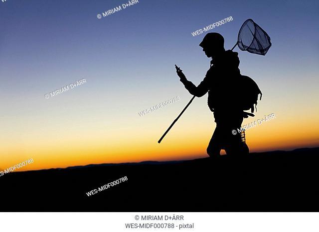 Female hiker carrying dip net and smart phone at dawn