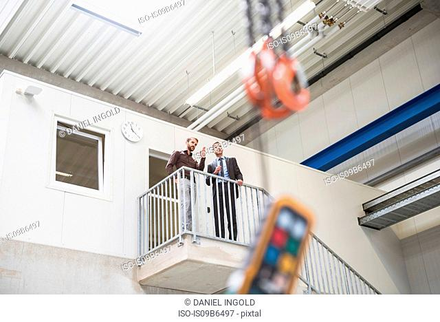 Supervisor and manager looking out from top of distribution warehouse stairway