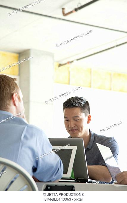 Businessmen using laptop computers in meeting