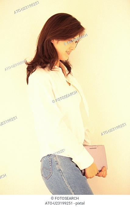 Image of a Young Adult Woman Holding a Laptop, Standing In Front of a White Wall, Side View