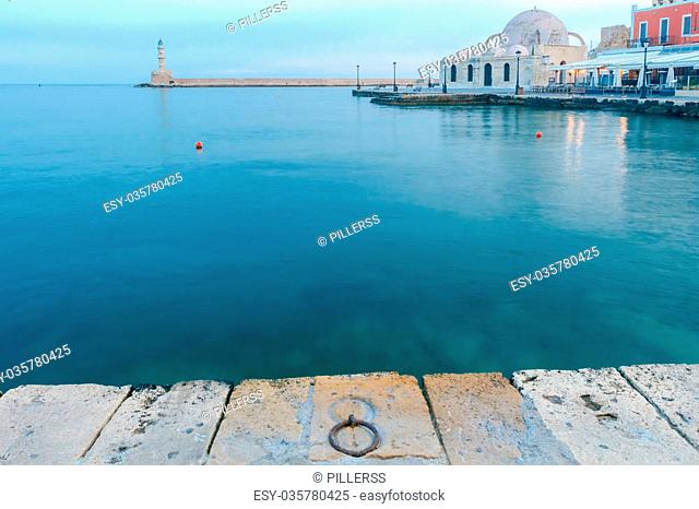 Scenic view of Venetian promenade with a lighthouse and the mosque Kucuk Hasan Pasha in the early morning, Crete, Greece