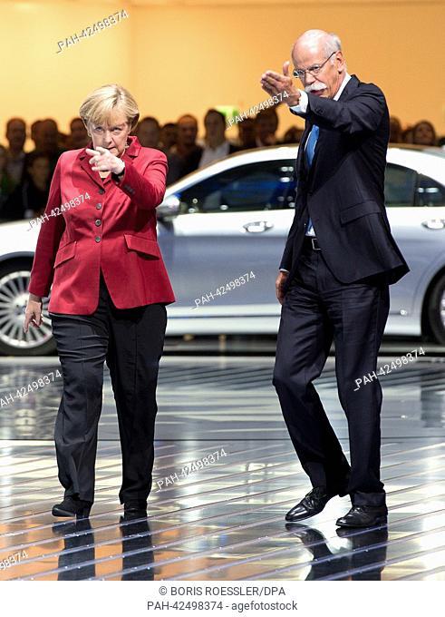 German Chancellor Angela Merkel (L) and CEO of Daimler Dieter Zetsche walk across a booth of Mercedes at the International Motor Show (IAA) in Frankfurt Main