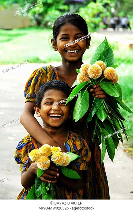 Two little girls posed for photograph They sell 'Kadam flowers' at the street Dhaka, Bangladesh 2007