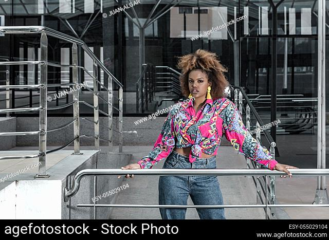Young independent African American curly haired female with tassel earrings dressed in bright shirt with knot and jeans standing near metal railing against...