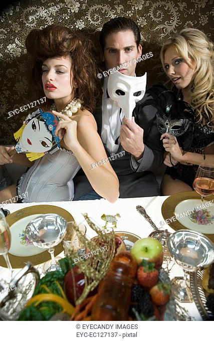 Portrait of sexy trio with masquerade masks at dinner party
