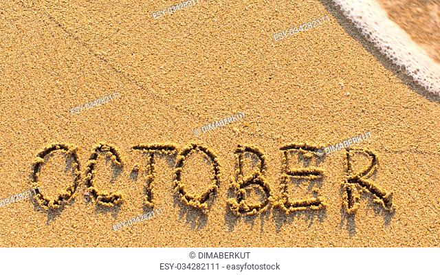 Inscription OCTOBER on a gentle beach sand with the soft wave (months of the year series)