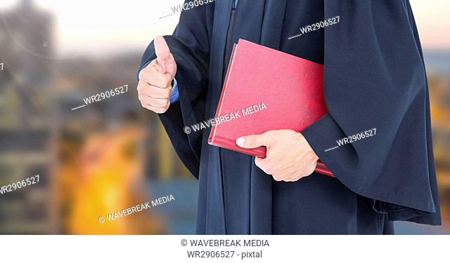 Judge holding book in front of city