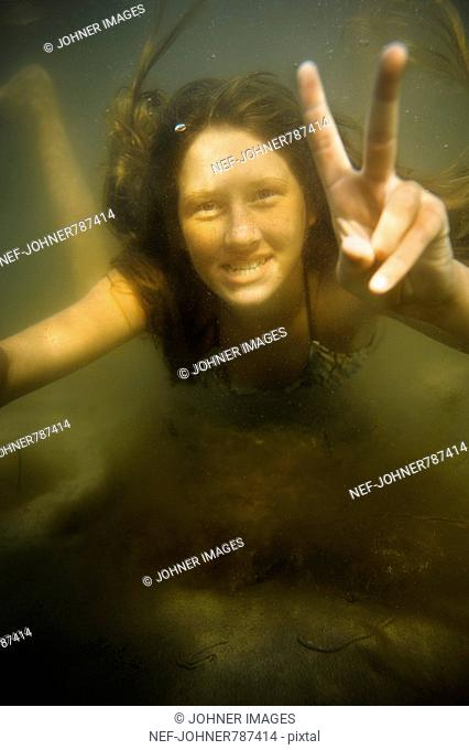 Girl making the victory sign under water, Sweden